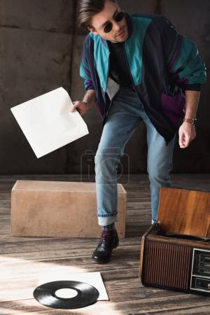 handsome young man in vintage windcheater with vinyl record player
