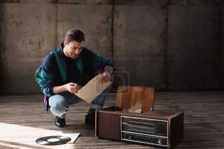 happy nostalgic young man in vintage windcheater with vinyl record player