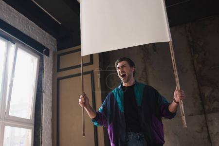 Photo pour Vue de dessous du jeune homme en colère criant dans windcheater vintage avec plaque vierge - image libre de droit