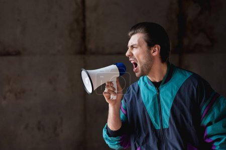 side view of angry young man in vintage windcheater shouting with loudspeaker