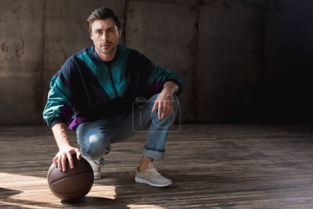 attractive young man in vintage windcheater with basketball ball sitting squats on wooden floor