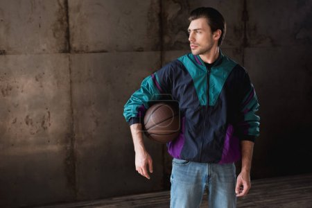 stylish young man in vintage windcheater with basketball ball looking away