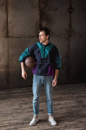 attractive young man in vintage windcheater with basketball ball looking away