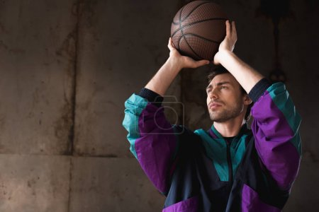 handsome young man in vintage windcheater throwing basketball ball