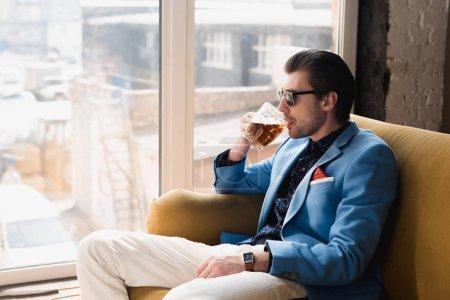 Photo pour Beau jeune homme en costume élégant assis sur le canapé et boire de la bière - image libre de droit