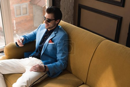 Photo for High angle view of smiling young man in stylish suit using smartphone while sitting on couch - Royalty Free Image
