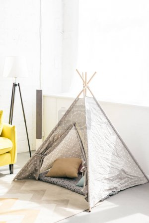 close up view of childish teepee with pillows in room