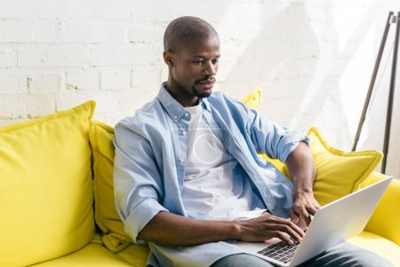 portrait of african american man using laptop on sofa at home