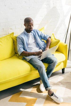 Photo pour Homme afro-américain en utilisant un ordinateur portable sur le canapé à la maison - image libre de droit