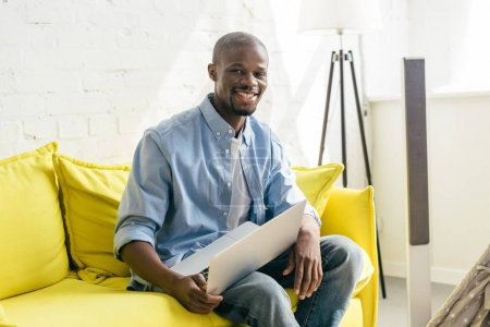 portrait of smiling african american man with laptop sitting on sofa at home