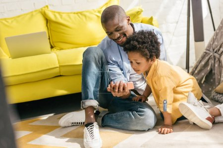 smiling african american and little son using smartphone together at home