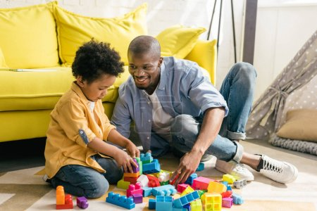 Photo for Smiling african american father and little son playing with colorful blocks together at home - Royalty Free Image
