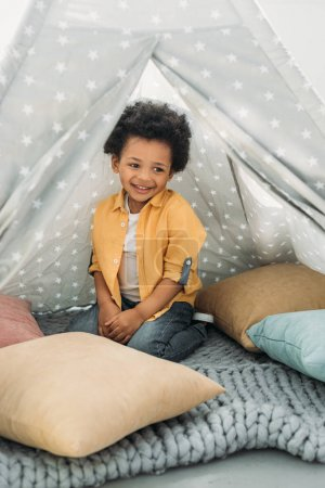 petit garçon afro-américain souriant assis en tipi à la maison