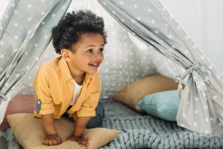 little smiling african american boy in teepee at home