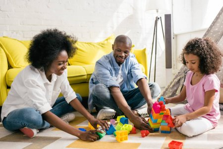african american family playing with colorful blocks together on floor at home