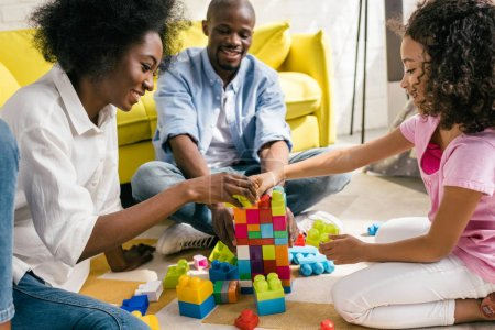 Photo for Happy african american family playing with colorful blocks together on floor at home - Royalty Free Image