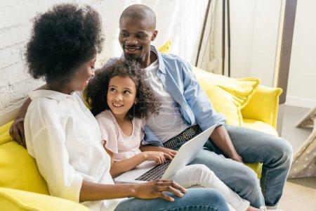 famille afro-américaine avec ordinateur portable reposant sur canapé ensemble à la maison