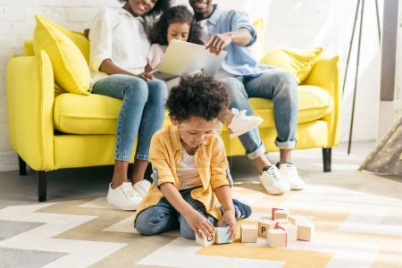 selective focus of little african american boy playing with wooden blocks while parents and sister using laptop on sofa at home