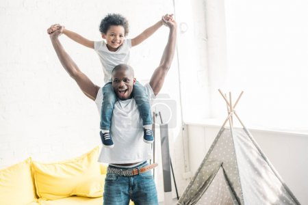 happy african american man playing together with little son at home