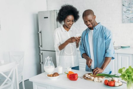 smiling african american man cooking breakfast and wife with smartphone standing near by in kitchen at home