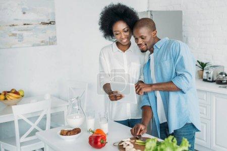 afroamericano usando tableta y verduras frescas en la mesa en la cocina en casa