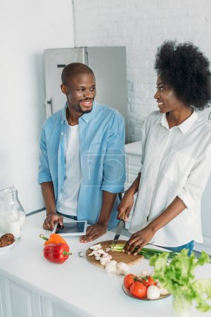 african american with tablet and fresh vegetables on table in kitchen at home