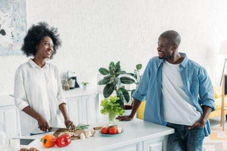 africano americano hombre mirando esposa cocina desayuno en cocina en casa