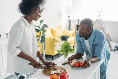 african american man looking at wife cooking breakfast in kitchen at home