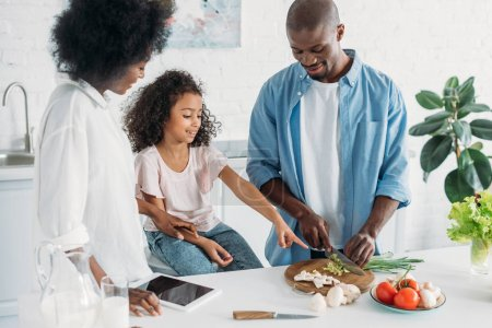african american man cutting fresh vegetables for breakfast with family standing near by in kitchen at home