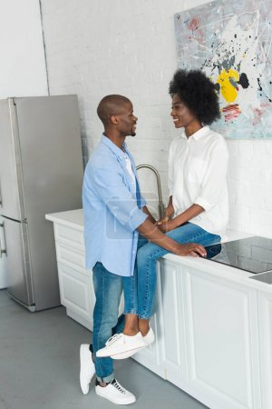 Photo for Smiling african american couple at counter in kitchen at home - Royalty Free Image