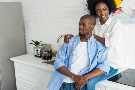 portrait of happy african american woman hugging husband in kitchen at home