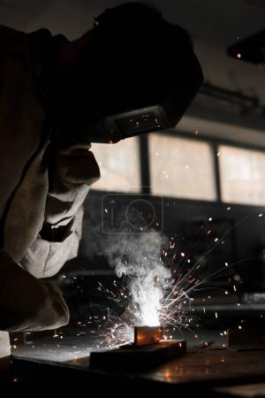 welder in protection mask working with metal at factory