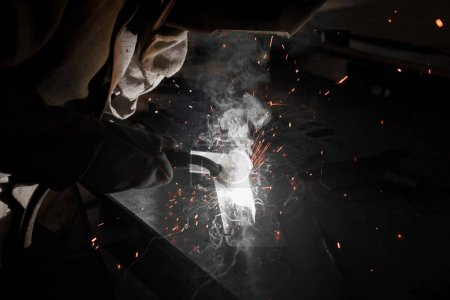 Photo for Cropped shot of worker in protection mask welding metal at factory - Royalty Free Image