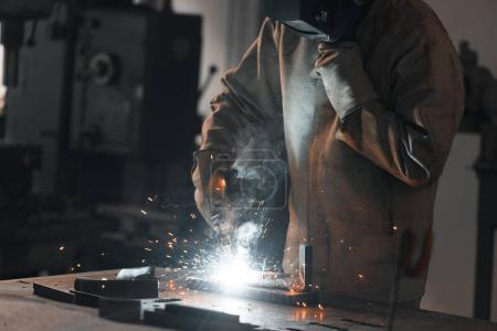 cropped shot of worker in protection mask welding metal at factory