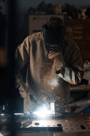 front view of welder in protection mask working with metal at factory