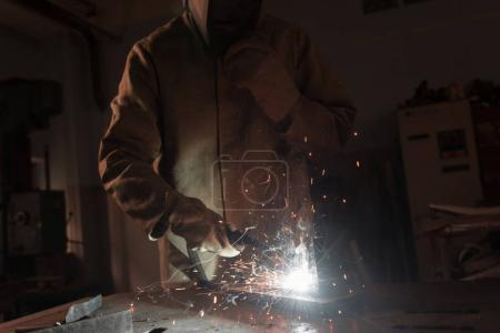 Photo pour Cropped image du travailleur au masque de protection métallique à l'usine de soudure - image libre de droit