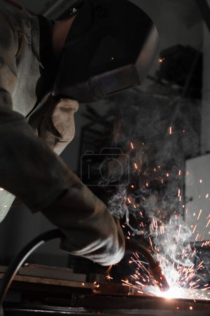 Photo for Manufacture worker welding metal with sparks at factory - Royalty Free Image