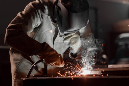 Photo for Worker in protection mask welding metal at factory - Royalty Free Image