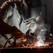 Worker in protection mask welding metal at factory...