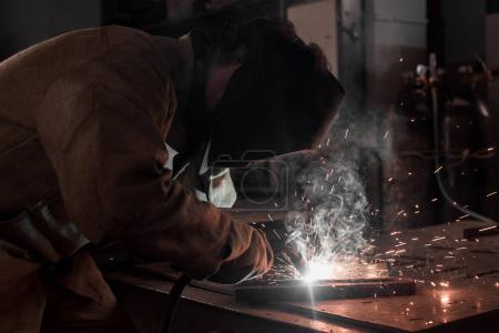 side view of worker in protection mask welding metal at factory