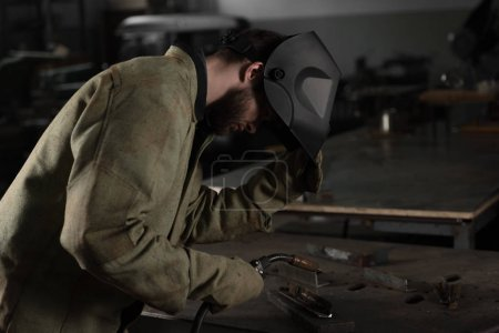 welder lifting up protective mask to look at his work at factory