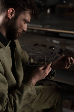 young male worker measuring metal part at factory