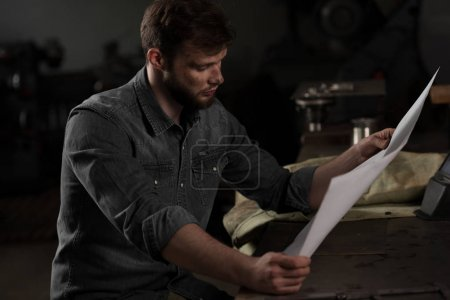 workman sitting at table and looking at blueprint