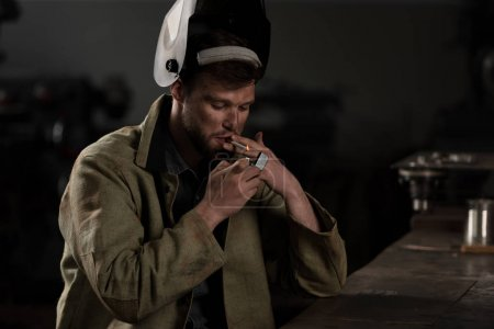 male worker with lifted up protective mask lightning cigarette at factory
