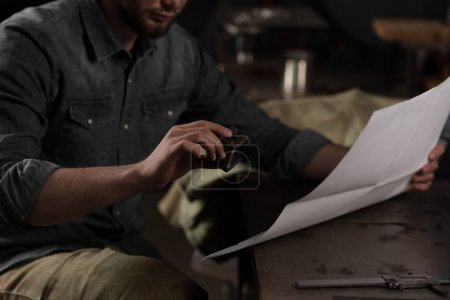 Photo pour Cropped image de jeune travailleur masculin assis avec blueprint en usine - image libre de droit