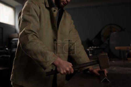 Photo pour Recadrée tir de partie métallique martelage de travailleur masculin à l'usine - image libre de droit