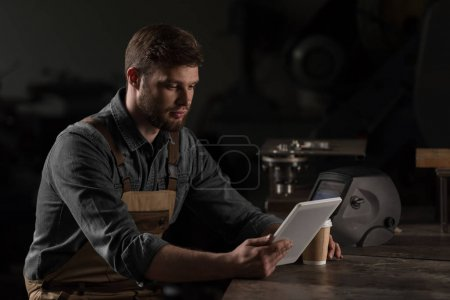 young male workman with paper cup of coffee using digital tablet