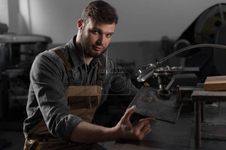portrait of young male worker in earphones holding metal part under magnifying glass