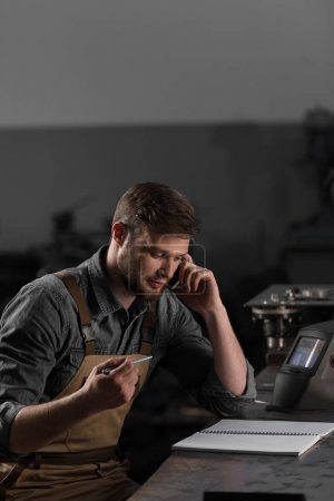 workman talking on smartphone and sitting at table with empty textbook
