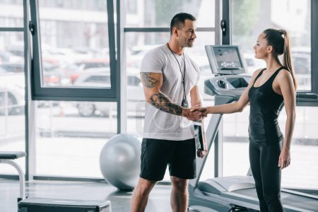 smiling male personal trainer and young sportswoman shaking hands at gym